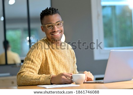 Portrait of cheerful ethnic guy working from home and having a coffee break Stockfoto ©