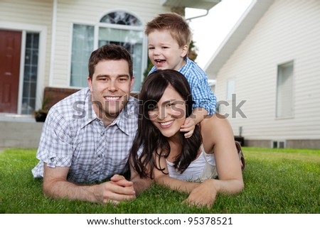 Portrait of cheerful family lying down on grass in front of house