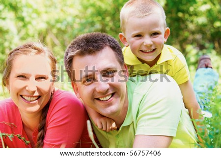 Portrait of cheerful family on summer vacation resting in park