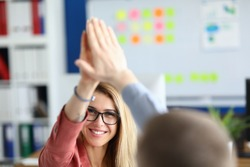 Portrait of cheerful female and male worker high five. Beautiful employee in modern office. Positive attitude for work. Happy event. Good deal or contract sign concept