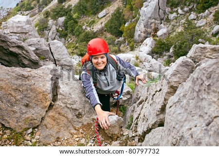 Portrait of cheerful female climber ascending a rock