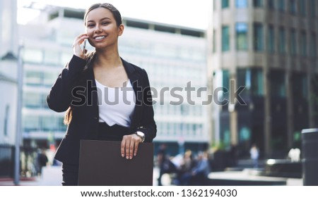 Portrait of cheerful female expert of management looking at camera during positive mobile conversation on publicity area, happy woman making good cellular call via application connected to 4g internet