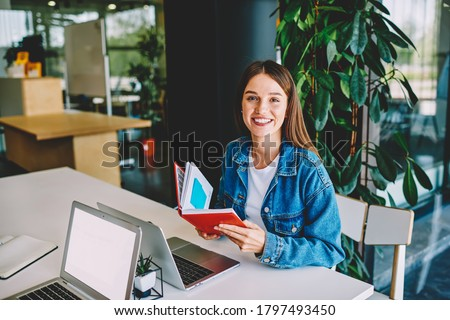 Portrait of cheerful female student with education notepad sitting at table desktop with modern laptop devices with copy space area for university website, happy woman with textbook posing indoors