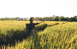 Portrait of cheerful female tourist with travel backpack pointing far away to rural landscape and smiling at camera, happy hipster girl in sunglasses enjoying solo travelling for visiting rice fields