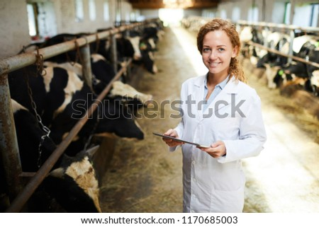 Portrait of cheerful female veterinarian smiling looking at camera while using digital tablet standing in cowshed of modern dairy farm, copy space