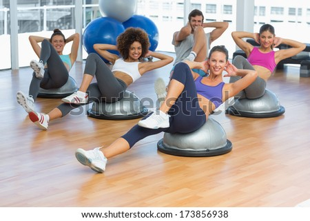 Portrait of cheerful fitness class doing pilates exercise in bright room