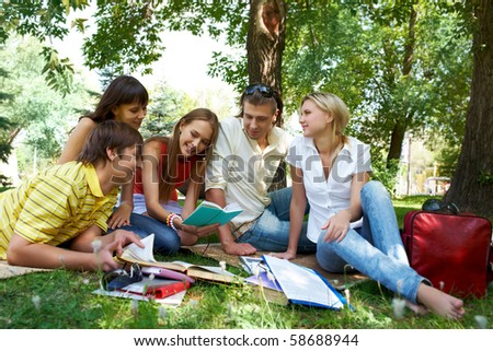 Portrait of cheerful friends listening to pretty girl while she reading outdoors