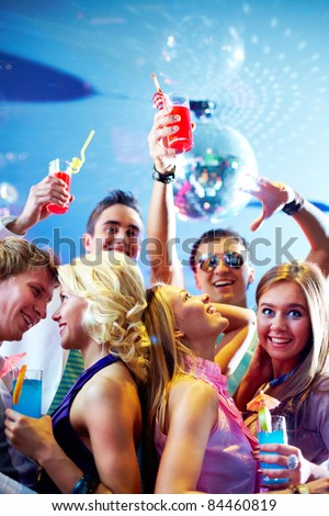 Portrait of cheerful friends with cocktails dancing and having fun in club