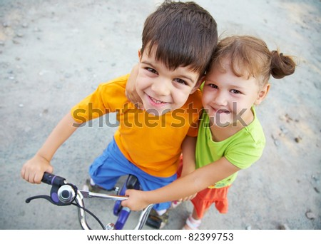 Portrait of cheerful girl and  fun boy with bike on the grey asphalt