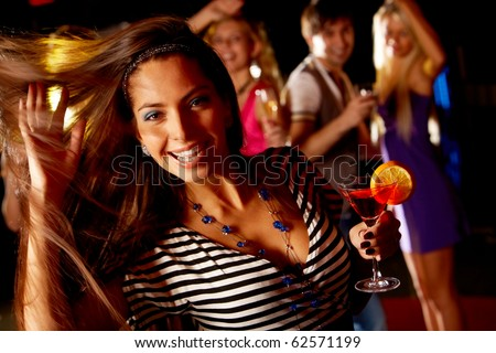 Portrait of cheerful girl dancing at party while smiling at camera