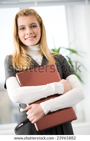 Portrait of cheerful girl holding laptop and looking at camera