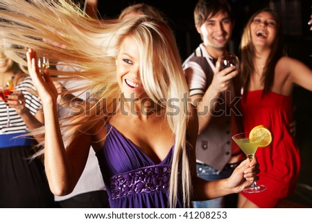 Portrait of cheerful girl with cocktail in hand having fun at discotheque