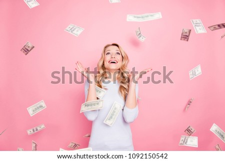 Portrait of cheerful glad girl enjoying shower from 100, hundred dollars, flying money, gesturing with hands isolated on pink background