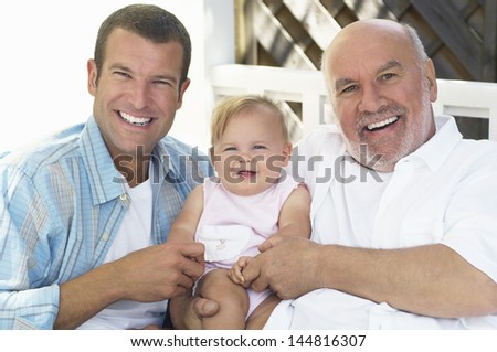 Portrait of cheerful grandfather with father and daughter