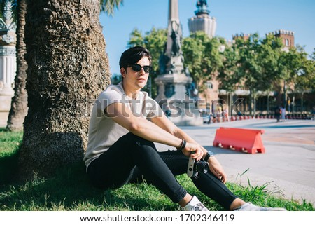 Photo of Portrait of cheerful handsome hipster guy sitting in park spending free time after quarantine period, smiling male traveler in sunglasses holding camera for taking pictures visiting town on holiday