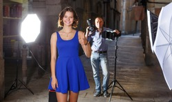 Portrait of cheerful happy girl on background with professional photographer during photo shoot on town street