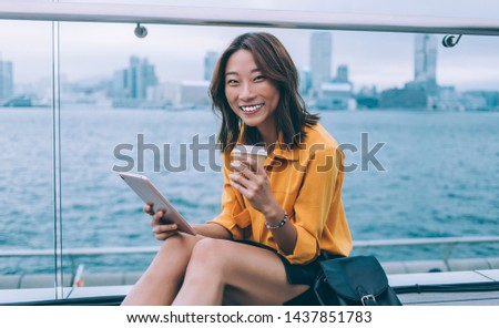 Portrait of cheerful hipster girl with modern digital tablet and coffee to go rejoicing outdoors enjoying Chinese vacations and time for exploring Hong Kong metropolis using 4g wireless for research #1437851783