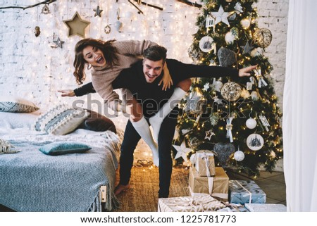 Portrait of cheerful hipster guy casual dressed looking at camera and laughing while joyful girlfrind having fun on his back, positive couple in Festive room with big Christmas tree and decorations #1225781773