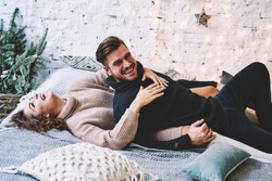 Portrait of cheerful hipster guy dressed in trendy apparel having fun with young wife on comfortable bed during free time indoors, happy caucasian couple laughing togetherness in cozy home space