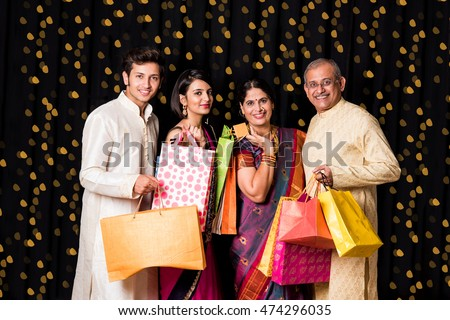 portrait of cheerful indian family with shopping bags in traditional wear in diwali isolated over black background with bokeh