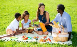 Portrait of cheerful interracial family with two children enjoying picnic on green meadow