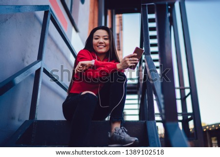 Portrait of cheerful japanese hipster girl dressed in casual wear listening audio music in modern earphones from playlist downloaded on smartphone device via public 4G internet, concept of generation #1389102518
