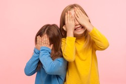 Portrait of cheerful joyful carefree little girls covering their faces with arms and sincerely smiling, laughing, having fun and playing peek a boo game. indoor studio shot isolated on pink background