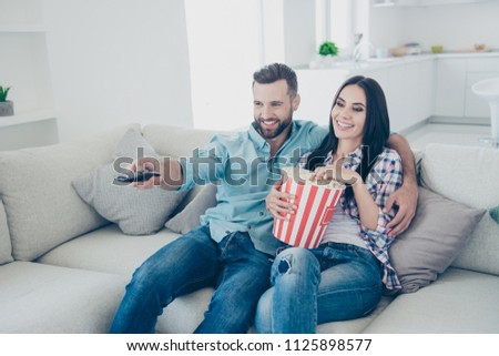 Portrait of cheerful joyful partners embracing sitting on sofa searching interesting program with remote control ready for watching comedy having snack bucket of popcorn
