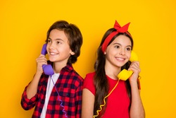Portrait of cheerful kids hand hold vintage handset receive call speak isolated on yellow color background