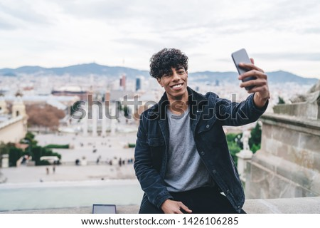 Portrait of cheerful Latino male traveller resting during Spanish vacations to Barcelona clicking selfie pictures on Montjuic area, millennial man photographing himself with cityscape on background #1426106285