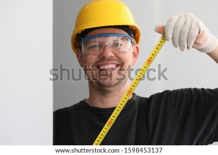 Portrait of cheerful male builder protected with yellow helmet and eyewear holding tape measure. Smiling man in gloves working on construction. Foreman concept