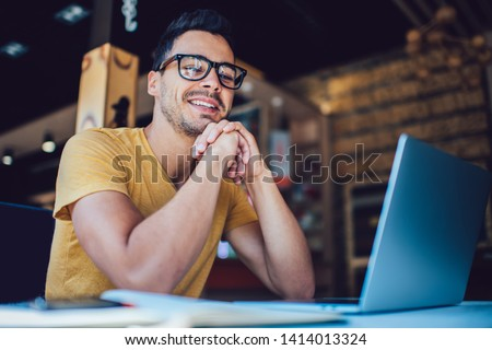 Portrait of cheerful male it professional working remotely with modern laptop device sitting at table and smiling at camera during break, happy man programmer in eyewear for vision correction
