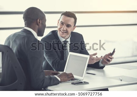 Portrait of cheerful male telling with colleague while holding phone in arm. Employer typing in laptop. Beaming associates talking during job concept #1069727756