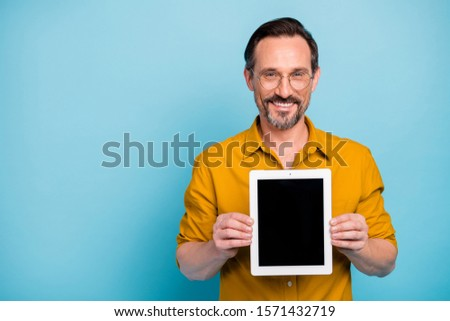 Portrait of cheerful man confident cool promoter hold tablet display gadget recommend adverts promotion wear yellow shirt isolated over blue color background