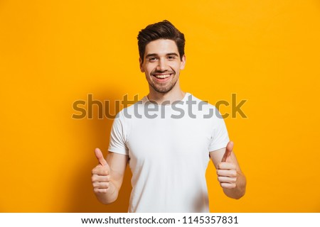 Portrait of cheerful man in basic clothing smiling and showing thumbs up at camera isolated over yellow background