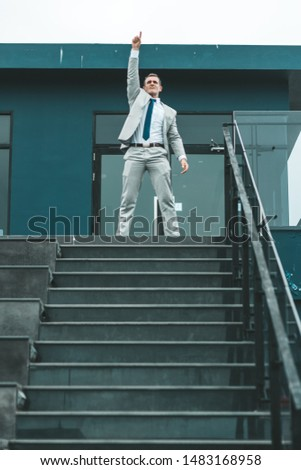 Portrait of cheerful middle-aged businessman standing near stairs. Experienced entrepreneur succeeded in achieving considerable results. Vertical shot #1483168958