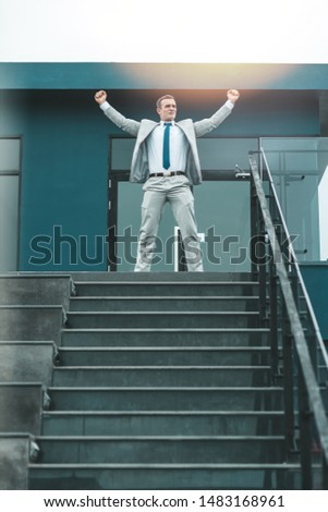 Portrait of cheerful middle-aged businessman standing near stairs. Experienced entrepreneur succeeded in achieving considerable results. Vertical shot #1483168961