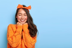 Portrait of cheerful mixed race woman has shy satisfied expression, smiles broadly, shows white teeth, wears orange bow headband and knitted sweater, poses against blue background. Ethnicity, emotions