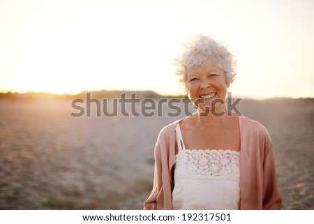 Portrait of cheerful old woman standing on the beach Smiling senior caucasian female smiling outdoors