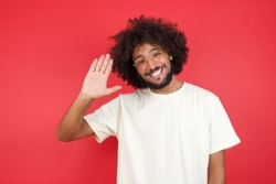 Portrait of cheerful, outgoing friendly-looking young man wearing casual clothes raise one hand and wave, saying hi or hello and smiling with carefree expression as make goodbye or welcome gesture.