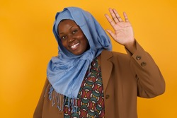 Portrait of cheerful, outgoing friendly-looking young woman wearing casual clothes raise one hand and wave, saying hi or hello and smiling with carefree expression as make goodbye or welcome gesture.