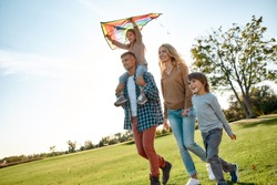 Portrait of cheerful parents with two kids walking with kite in the park on a sunny day. Family, kids and nature concept. Horizontal shot. Front view. Dutch angle