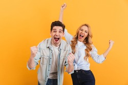 Portrait of cheerful people man and woman in basic clothing smiling and clenching fists like winners or happy people isolated over yellow background