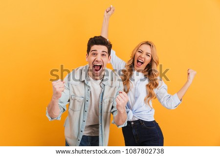 Portrait of cheerful people man and woman in basic clothing smiling and clenching fists like winners or happy people isolated over yellow background #1087802738