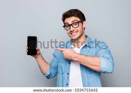 Portrait of cheerful, positive, attractive guy with stubble in jeans shirt, having smart phone with black screen in hand, pointing with forefinger to product, isolated on grey background