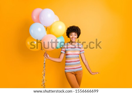 Portrait of cheerful positive cheerful afro american girl hold many colorful air baloons enjoy summer anniversary holidays wear casual style clothing isolated over shiny color background #1556666699