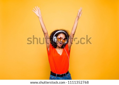 Portrait of cheerful positive chic holding raised arms having headphones on head listening music singing song enjoying weekend vacation isolated on yellow background