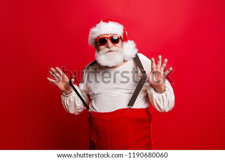 Portrait of cheerful positive dreamy funky Santa congratulations best wishes pulling suspenders ready to feast congrats isolated over bright vivid red background #1190680060