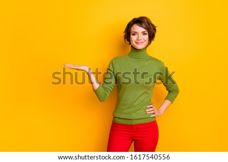 Portrait of cheerful positive girl promoter hold hand show adverts promotion present sales discount wear good look clothes isolated over shine color background