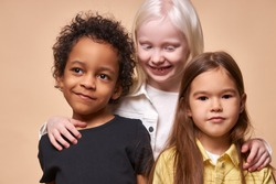 portrait of cheerful positive kids, multiethnic children isolated in studio. adorable africanamerican black boy and albino, caucasian girls stand together, posing. international friendship